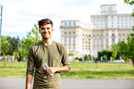 handsome young man drinking a bottle of water outside
