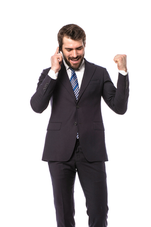 corporate man, elegant businessman standing on white background geting the good news on cellphone Banque d'images - 114110913
