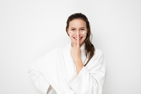 Young woman with flawless skin, applying moisturizing cream on her face. Playing with cream and making lines on her face. Photo of woman after bath in white bathrobe and towel on white background. Skin care concept Stock Photo