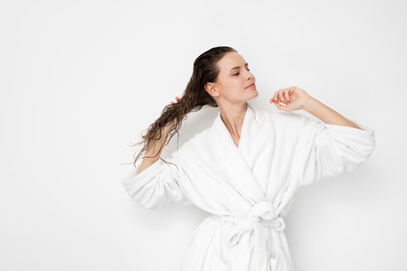 young natural and beauty woman happy after a hair treatment, holding or touching her hair with joy and pleasure in bathrobe on white background