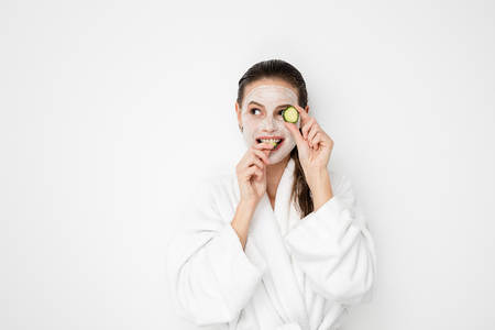 Beautiful young girl with moisturizing facial mask on white background. Photo of girl in bathrobe after shower doing her treatments and playing with cucumber slices. Skin care concept