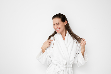 young natural and beauty woman standing with wet hair after a shower or a hair treatment in bathrobe on white background