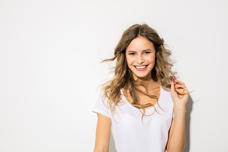 portrait of young and beautiful woman, expressive face, in white shirt smiling to camera