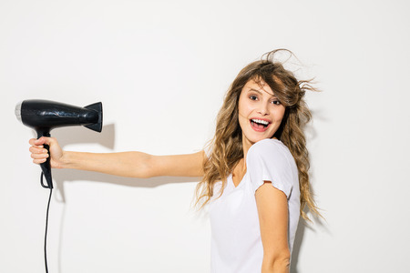 young funny woman blowing her hair with a hair drayer on white background
