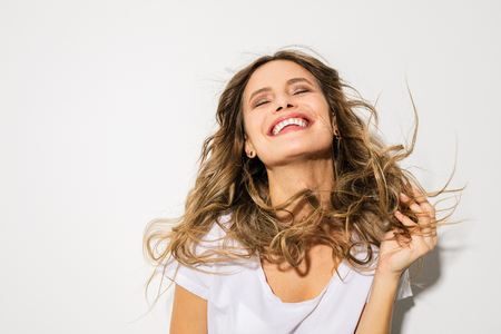 young woman with blowing hair smiling with joy on white background Banco de Imagens
