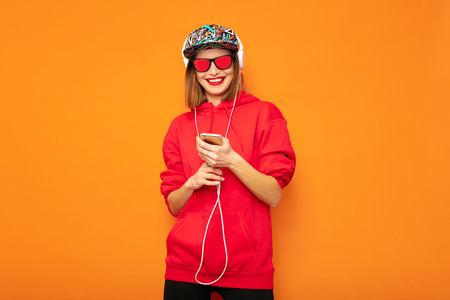 cool hipster girl looking at her cellphone and listening music on headphones, wearing colored hat on orange background Stock Photo - 116589403