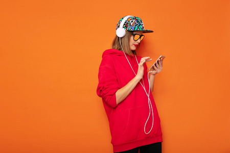 cool hipster girl looking at her cellphone and listening music on headphones, wearing colored hat on orange background 版權商用圖片