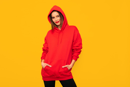 cool young woman posing with a red hoodie, hipster woman on yellow background Archivio Fotografico