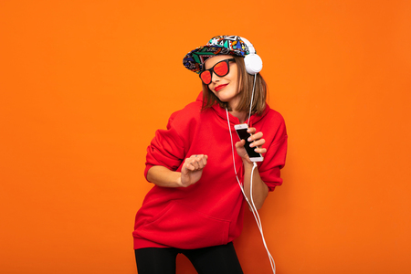dancing cool hipster hirl with colored hat and headphones, having fun was never so easy