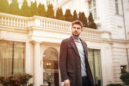 confident and stylish man standing outside in front of a hotel or a nice old building