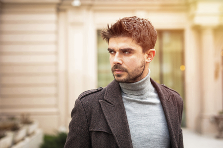 portrait of a young and stylish man, outside, looking confident in front of nice old building