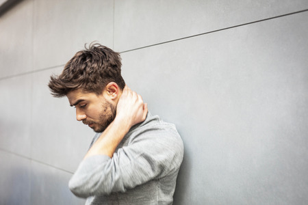 pain on neck, young man having hands on his neck on gray wall