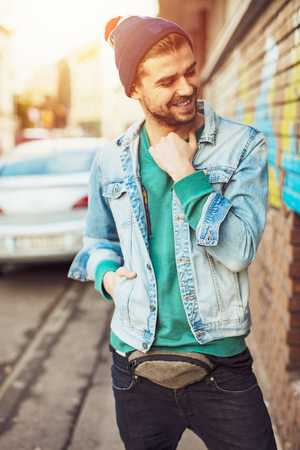 being cool was never easy, young man with beard dressed in a cool young posing to camera with smile, modern hipster Imagens
