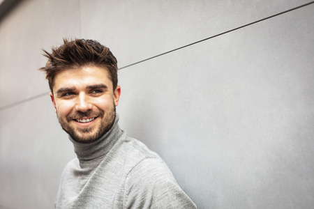 smiling attractive man on gray modern wall