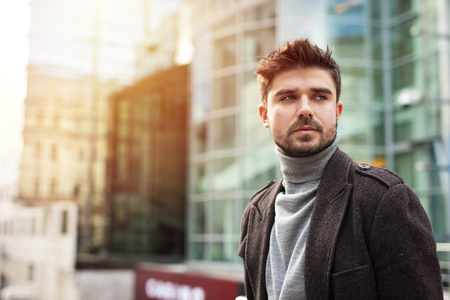 dream big, young and confident guy, hansome and attractive posing outside with office building in background