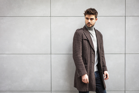 young attractive man in coat posing on a grey wall , stylish man