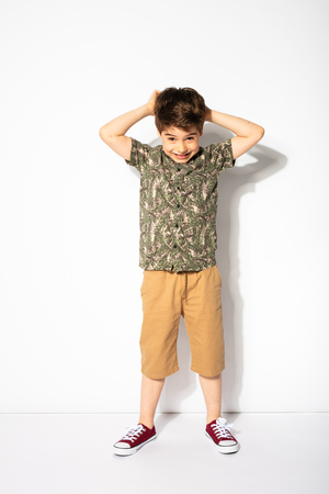 trouble little boy posing on white background, thinking about what he did wrong Stock fotó