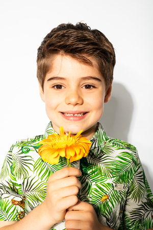spring is here, happy kid posing with a flower on white background