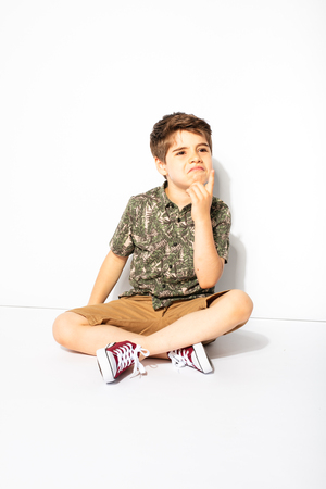 expressive little boy posing while sitting down on white background, thinking about something or having a conversation 版權商用圖片