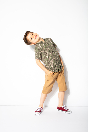 funny kid fooling around and smiling to camera on white background Zdjęcie Seryjne