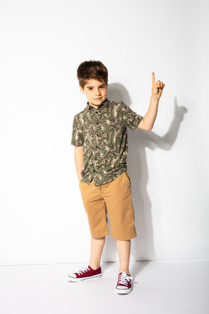 have an ideea. little boy pointing his finger up, like he got an idea, posing on white background