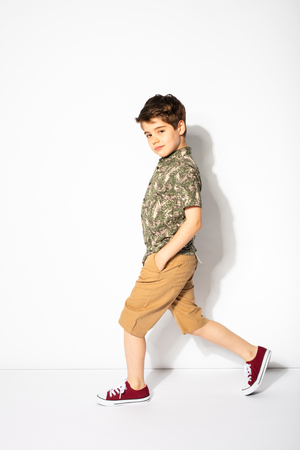 funny little boy walking and smiling to camera on white background Zdjęcie Seryjne