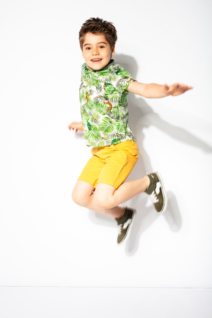 little boy jumping and smiling on white background Zdjęcie Seryjne