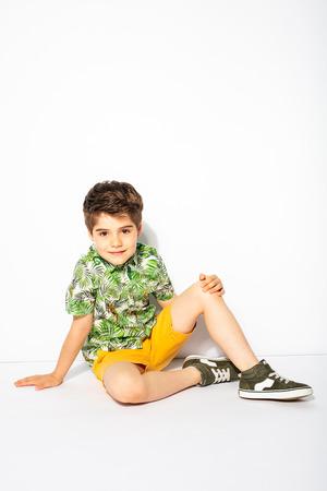little energetic kid sitting on the floor and looking to camera with smile Zdjęcie Seryjne