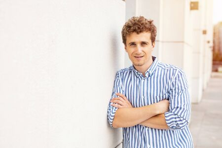 smart casual man standing against a white wall of a buiding looking with confidence to camera