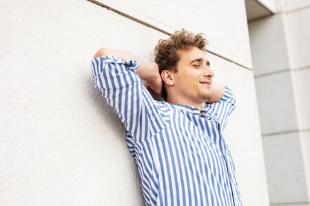 successful man standing very relax on a white wall and looking to camera
