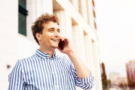clouse up portrait of a handsome man having a nice conversation at cellphone outside, smiling and enjoying talking