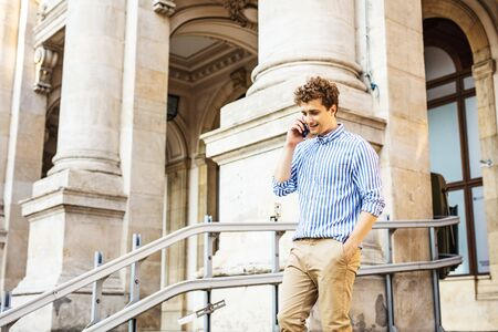 young man walking and having a conversation  at cellphone at the entrance of an old building Stockfoto