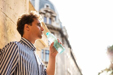 young man in elegant shirt drinking water next to an old wall, feeling the heat of the sun Stockfoto