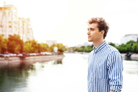 handsome young man walking along river in a european city, traveling or going to work Stock Photo