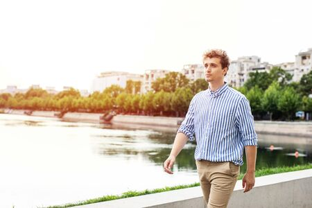 handsome young man walking along river in a european city, traveling or going to work Stockfoto