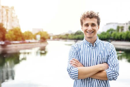 young man smart casual dressed looking with confidence to camera having a river behind, standing with arms crossed