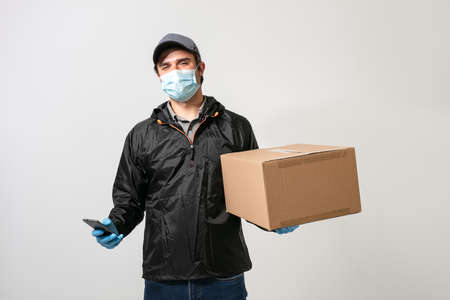 delivery man wearing medical protection against infection, carrying a package on grey background Foto de archivo