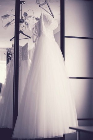 mirror image: Wedding white dress hangs on a hanger near the mirror. Monochrome image.