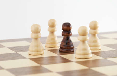 Chess pawn on chessboard with white background. Landscape format. photo