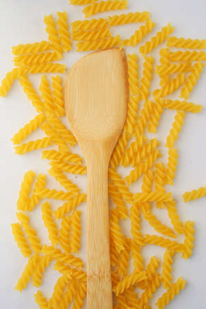 Rotini Pasta and wooden spoon. Above view. photo