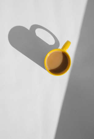 coffee mug with cappuccino on light grey background. Mimimalistic studio shoot. Above view photo