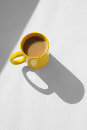 coffee mug with cappuccino on light grey background. Mimimalistic studio shoot. High Angle View photo