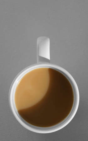 coffee mug with cappuccino on grey background. Mimimalistic studio shoot. Above view photo