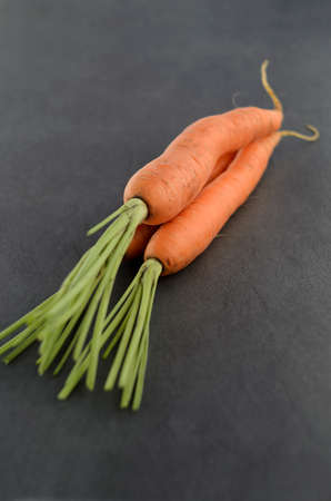 Bunch of carrots on dark textured background. Selective Focus. Narrow depth of field. photo