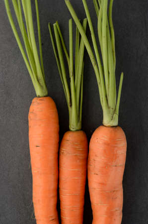 Bunch of carrots on dark textured background. Above view. Selective Focus. Narrow depth of field. photo