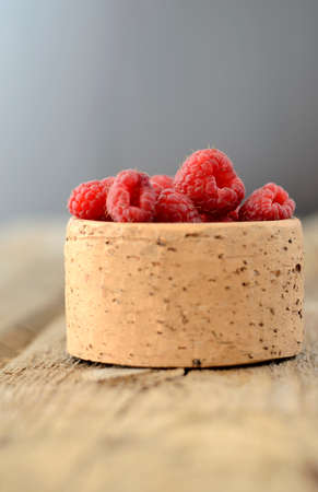 Bowl of Raspberries on textured wood background. Shallow depth of field. photo