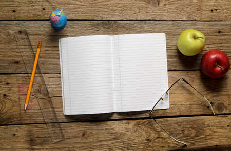 Back to school background. Blank notebook and different school objects. Above view. photo