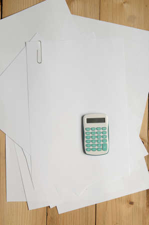 blank papers: Calculator and blank papers on wood background. Above view. Stock Photo