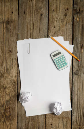 blank papers: Blank papers, calculator and pencil on dark background. Above view. Stock Photo