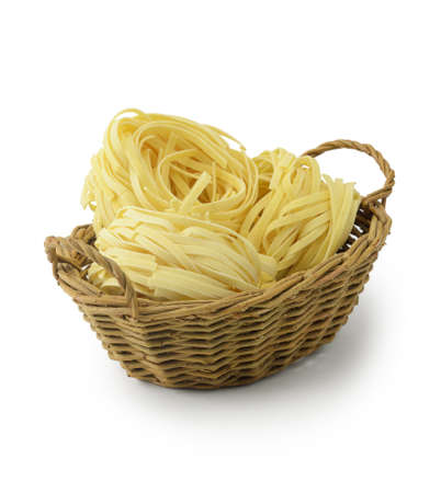 Tagliatelle pasta in basket isolated on white background photo